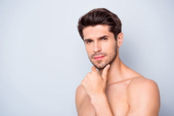Close up photo of attractive focused guy look mirror touch unshaven, chin skin need skincare cosmetics treatment isolated over grey color background