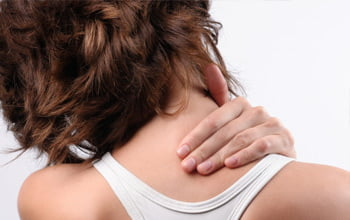 woman touching back of her neck, indicating tension