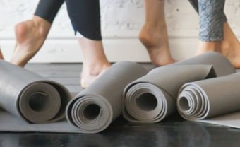 Photo of women's feet in a fitness class with rolled up yoga mats in the foreground
