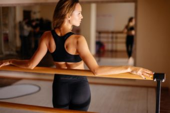 Woman in black workout attire leaning up against a ballet barre in a fitness studio