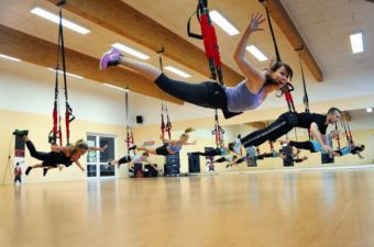 Photo of a bungee fitness class with several attendees hanging via hip harness and bungees from the ceiling of a fitness studio