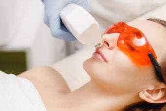 Master carries out removal of unwanted hair laser on face young woman. Health and beauty concept