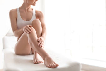 Young woman showing smooth silky legs after laser hair reduction