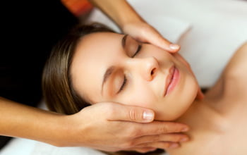 massage therapist touching womans face